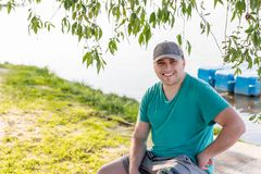 Young confident attractive man in casual dress and cap sitting and smiling at river or lake shore. Camping and travel royalty free stock photography