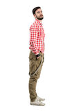 Young confident bearded hipster side view with hands in pockets royalty free stock photography