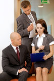 Young confident boss and his secretary looking on documents Stock Photo