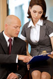 Young confident boss and his secretary looking on documents Royalty Free Stock Photo