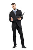 Young confident business man holding document folder with thumb up gesture. Full body length portrait isolated over white studio background royalty free stock photos