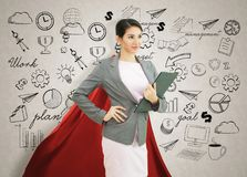 Young confident business superhero woman wearing red cape agains. T with strategy background. concept point to future royalty free stock photos