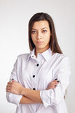 Young Confident business Woman. Portrait of a young serious business woman, standing with folded hands, against white background Stock Images