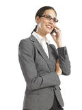 Young confident business woman speaking on phone. With her arm crossed Royalty Free Stock Photo