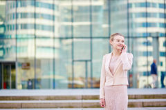 Young confident business woman using phone. Young confident business woman in modern glass office interior using the mobile phone Stock Photo