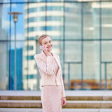 Young confident business woman using phone. Young confident business woman in modern glass office interior using the mobile phone Royalty Free Stock Photos