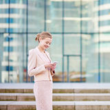 Young confident business woman using phone. Young confident business woman in modern glass office interior using the mobile phone Royalty Free Stock Image
