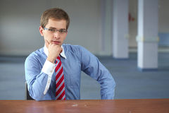 Young confident businessman in blue shirt sits Stock Image