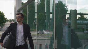 Young confident businessman in glasses and with suitcase in modern airport terminal on the glass wall background stock video