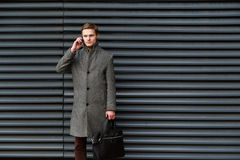 Young confident businessman in a gray coat and briefcase in his hand is talking on mobile phone against wall of modern stock photos