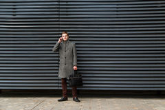 Young confident businessman in a gray coat and briefcase in his hand is talking on mobile phone against wall of modern royalty free stock photos