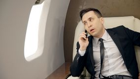 Young confident businessman is making mobile call, sitting in first class airplane. Young confident businessman is making mobile call, sitting in first class stock footage