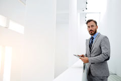 Young confident businessman with portable digital tablet in hands is looking at camera stock image
