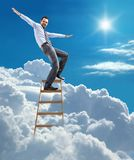 Young confident businessman standing at the ladder high in the sky balancing on top. Young man in shirt and tie pulls his arms out to the side like an airplane Stock Images