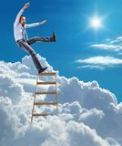 Young confident businessman standing at the ladder high in the sky falls from the top. Young man in shirt and tie extends slipped and falls from the top of Stock Photo