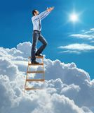 Young confident businessman standing at the ladder high in the sky pulls hands to the sky. Young man in shirt and tie pulls hands to the sky on top of the ladder Stock Photo