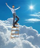 Young confident businessman standing at the ladder high in the sky spread his arms Royalty Free Stock Photos