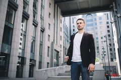 A businessman in city. Young and confident businessman is standing near the office building. He is looking somewhere aside and thinking about the rest of the Royalty Free Stock Image