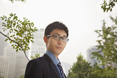 Young confident businessman standing in the park, portrait Royalty Free Stock Image