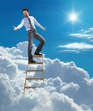 Young confident businessman standing at the top of ladder high in the sky lends a helping hand royalty free stock image