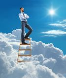 Young confident businessman standing at the top of ladder high in the sky and looking for new opportunities. Young man in shirt and tie stands with his arms Royalty Free Stock Photo