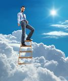 Young confident businessman standing at the top of ladder high in the sky and showing down by the hand with forefinger Royalty Free Stock Photography