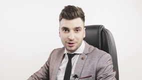 Young confident businessman or TV presenter with lapel microphone looking at camera and talking. Slow motion stock video footage