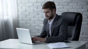 Young confident businessman typing e-mail on laptop, solving business issues royalty free stock photos