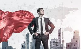Concept of power and sucess with businessman superhero in big ci. Young confident businessman wearing red cape against modern city background royalty free stock image