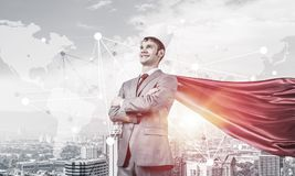 Concept of power and sucess with businessman superhero in big ci. Young confident businessman wearing red cape against modern city background stock photos