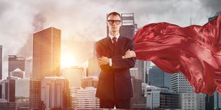 Concept of power and sucess with businessman superhero in big city. Young confident businessman wearing red cape against modern city background royalty free stock photo