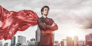 Concept of power and sucess with businessman superhero in big city. Young confident businessman wearing red cape against modern city background royalty free stock image