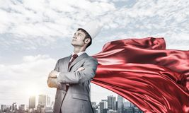 Concept of power and sucess with businessman superhero in big city. Young confident businessman wearing red cape against modern city background royalty free stock photography