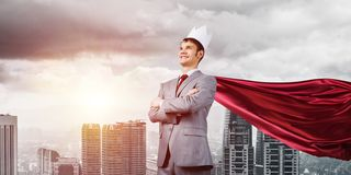 Concept of power and sucess with businessman superhero in big city. Young confident businessman wearing red cape against modern city background royalty free stock images
