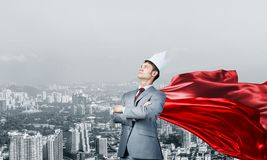 Concept of power and sucess with businessman superhero in big city. Young confident businessman wearing red cape against modern city background royalty free stock photos
