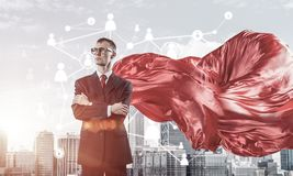 Concept of power and sucess with businessman superhero in big ci. Young confident businessman wearing red cape against modern city background royalty free stock photos