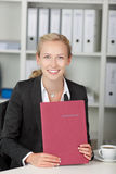 Young Confident Businesswoman Holding Application File At Desk Royalty Free Stock Photos