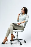Young confident businesswoman sitting on the office chair with pen and tablet computer. On gray background Stock Photos