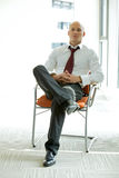 Young confident caucasian businessman sitting on office chair Stock Photos