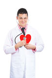 Young confident doctor with stethoscope at a heart against his chest Stock Photography