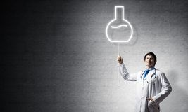Doctor and vial symbol. Young confident doctor in white medical uniform interracting with glowing vial symbol whie standing against dark gray wall on background royalty free stock photos