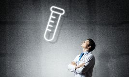 Doctor and vial symbol. Young confident doctor in white medical uniform interracting with glowing vial symbol whie standing against dark gray wall on background stock photography