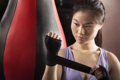 Young confident female boxer wrapper her wrists in the gym Stock Photos