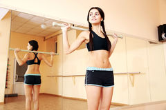 Young confident fit woman working out with gymnastic stick Royalty Free Stock Photos