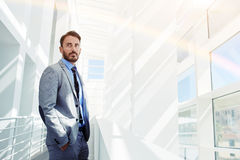 Young confident male ceo dressed in elegant clothes posing while standing in modern office building Stock Photography