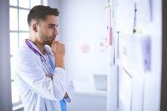 Young and confident male doctor portrait standing in medical office.  Stock Photos