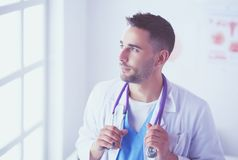 Young and confident male doctor portrait standing in medical office. Young and confident male doctor portrait standing in medical office Royalty Free Stock Photo