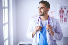 Young and confident male doctor portrait standing in medical office.  Stock Photography
