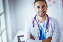 Young and confident male doctor portrait standing in medical office.  Royalty Free Stock Photo