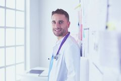 Young and confident male doctor portrait standing in medical office. Young and confident male doctor portrait standing in medical office Stock Image